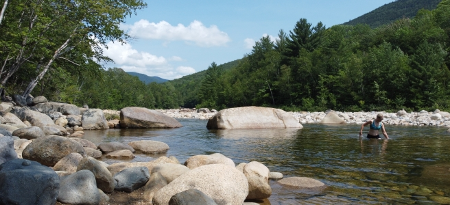 The author is standing in the mountain river surrounded by green mountains and trees.